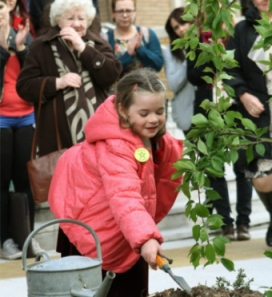 Isla helping to plant a tree in memory of Jane
